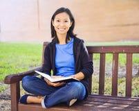 Молодая женщина при длинние волосы сидя в чтении сиденья у окна Стоковое фото RF