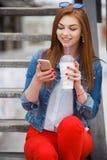 Молодая женщина при коктеиль, читая текстовое сообщение на улице Стоковые Фотографии RF