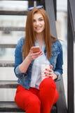 Молодая женщина при коктеиль, читая текстовое сообщение на улице Стоковое Фото