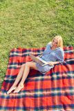 Молодая женщина при компьтер-книжка сидя в траве луга зеленой Стоковое фото RF