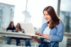 Молодая женщина при компьтер-книжка стоя в интерьерах кафа Стоковая Фотография RF