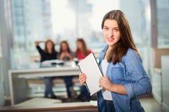 Молодая женщина при компьтер-книжка стоя в интерьерах кафа Стоковые Изображения RF