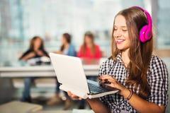Молодая женщина при компьтер-книжка стоя в интерьерах кафа Стоковое Изображение RF