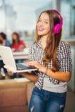 Молодая женщина при компьтер-книжка стоя в интерьерах кафа Стоковые Фотографии RF
