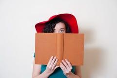 Молодая женщина при красная частично покрытая сторона книги чтения шляпы Стоковое Изображение
