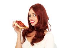 Молодая женщина при красные волосы держа кусок варенья клубники на здравице Стоковое фото RF