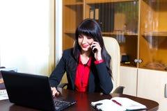 Молодая женщина при мобильный телефон сидя на столе Стоковые Фото