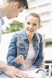 Молодая женщина при мужской друг изучая совместно на кампусе коллежа Стоковое Изображение RF