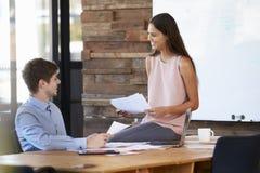 Молодая женщина при обработка документов сидя на столе ` s человека в офисе Стоковые Изображения RF