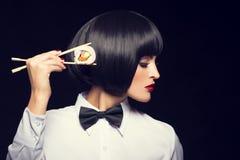Молодая женщина при парик держа суши Стоковые Изображения RF