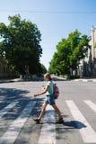 Молодая женщина при рюкзак и кофе пересекая улицу Стоковое Изображение