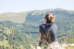 Молодая женщина при рюкзак сидя на крае скалы и смотря к Стоковые Фотографии RF