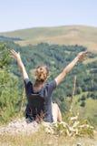 Молодая женщина при рюкзак сидя на крае скалы и смотря к Стоковое Изображение
