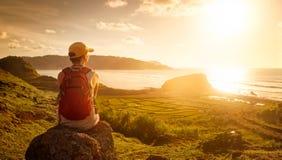 Молодая женщина при рюкзак сидя на скале и смотря к солнца стоковая фотография rf
