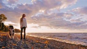 Молодая женщина при собака стоя рядом с берегом озера или моря На заходе солнца, смотрящ в расстояние, мечтая сток-видео