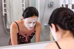 Молодая женщина при сторона косметической маски моя стоя перед Стоковое Изображение