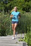 Молодая женщина при след музыки бежать для свободы и выносливости Стоковая Фотография RF