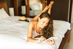 Молодая женщина при таблетка лежа на кровати Стоковая Фотография RF