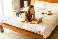 Молодая женщина при таблетка лежа на кровати Стоковое Фото