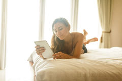 Молодая женщина при таблетка лежа на кровати Стоковые Изображения