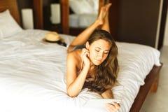 Молодая женщина при таблетка лежа на кровати Стоковая Фотография