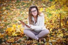 Молодая женщина при таблетка сидя в парке осени Стоковое Изображение