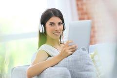 Молодая женщина при таблетка сидя на софе Стоковые Фото