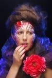 Молодая женщина при художническое выражение лица держа большой красный цветок Стоковое фото RF