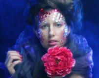Молодая женщина при художническое выражение лица держа большой красный цветок Стоковые Изображения