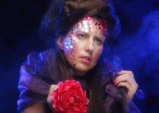 Молодая женщина при художническое выражение лица держа большой красный цветок Стоковое Изображение
