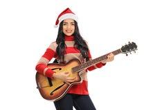 Молодая женщина при шляпа Санты играя гитару Стоковые Изображения RF