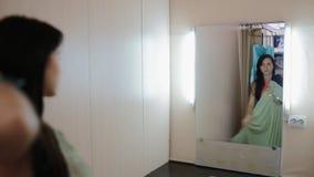 Молодая женщина пробует дальше платья в уборной акции видеоматериалы