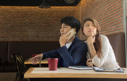 Молодая женщина пробуя слушать сплетня/любознательная девушка слушая к ее парню говоря на телефоне стоковая фотография