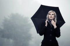 Молодая женщина с зонтиком против помоха Стоковые Изображения RF