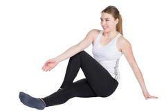 Молодая женщина протягивает ее мускулатуру стоковое изображение
