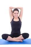 Молодая женщина протягивая руки на циновке йоги изолированной на белом backg Стоковое Изображение
