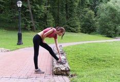 Молодая женщина протягивая outdoors в после полудня Стоковое фото RF