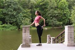 Молодая женщина протягивая outdoors в после полудня Стоковые Изображения