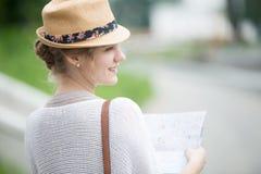 Молодая женщина путешественника в соломенной шляпе держа карту Задний взгляд со стороны Стоковые Фотографии RF