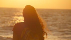 Молодая женщина путешественника стоя на береге океана и смотря восход солнца Молодой женский турист с рюкзаком наслаждаясь взгляд Стоковое фото RF