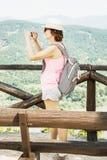 Молодая женщина путешественника фотографируя с smartphone в бросании руин Стоковое Фото