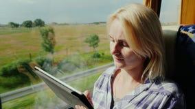 Молодая женщина путешествует шиной, наслаждается таблеткой Вне окна живописный район, шина быстро едет видеоматериал