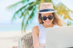 Молодая женщина работая в компьтер-книжке на пляже Работать работа Стоковое Изображение RF