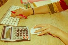 Молодая женщина работая в офисе, сидя на столе, используя компьютер стоковое фото rf