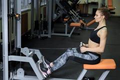 Молодая женщина работая назад на машине в спортзале и изгибая мышцы - мышечную атлетическую модель фитнеса культуриста Стоковая Фотография