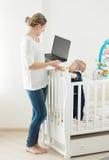 Молодая женщина работая на компьтер-книжке и позаботить о младенец Стоковые Изображения RF
