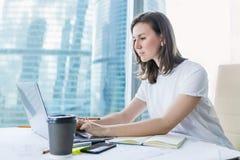 Молодая женщина работая на компьтер-книжке на офисе Стоковые Фотографии RF