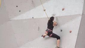Молодая женщина работая на крытой взбираясь стене спортзала движение медленное Альпинисты тренировки на взбираясь стене девушка и акции видеоматериалы