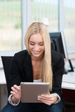 Молодая женщина работая на таблетке в офисе Стоковая Фотография