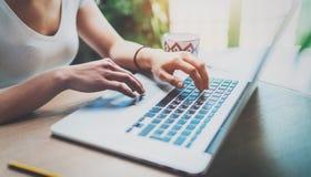 Молодая женщина работая дома на современном компьютере пока сидящ на деревянном столе Женские руки печатая на клавиатуре компьтер Стоковое фото RF